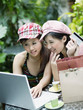 Two women on outdoor patio with credit card and laptop