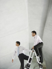 Two businessmen on ladder in structure