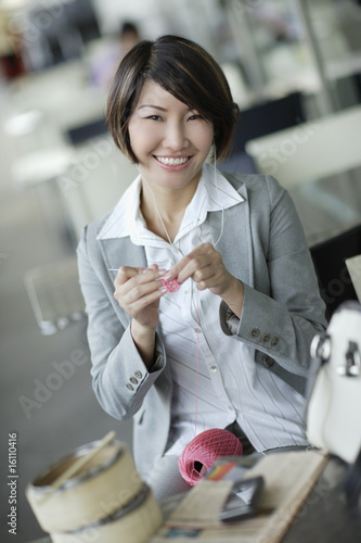 Businesswoman in cafeteria wearing ear buds and crocheting