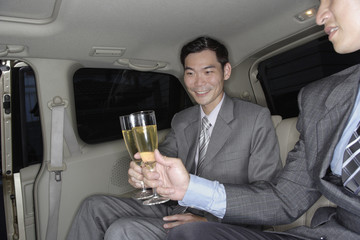 Two businessmen in limousine toasting champagne flutes