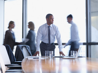 Businessman in boardroom with three co-workers behind him