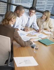 Four businesspeople at a boardroom table with paperwork