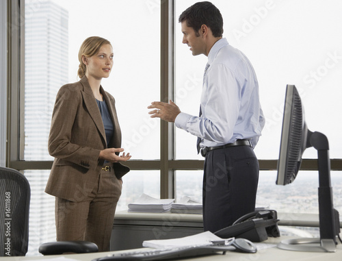 Businessman and businesswoman in an office talking