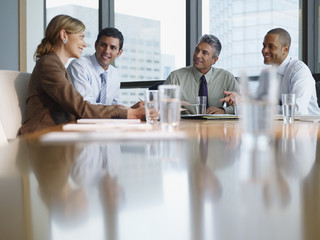 Four businesspeople in a boardroom working