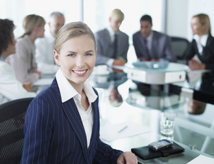 Six businesspeople in boardroom with businesswoman in foreground