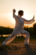 woman in white suit make's taiji chuan exercise - 7