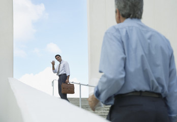Two businessmen walking up an outdoor staircase