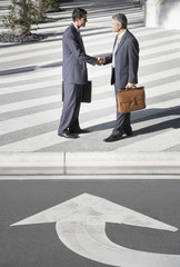 Two businessmen outdoors shaking hands by street with arrow pointing towards them