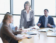 Four businesspeople in boardroom with one in focus
