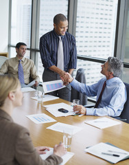 Two businessmen in boardroom shaking hands with two co-workers watching