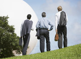 Three businessmen outdoors by a large white sphere