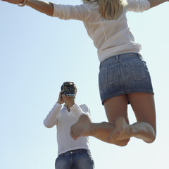 Man taking a picture of a woman jumping outdoors
