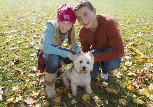 Young boy and young girl outdoors with a dog