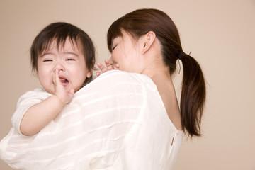 母親に抱っこされながら泣いている赤ちゃん