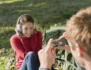 Man outdoors taking a picture of a woman with digital camera