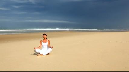 Femme méditant sur le sable dos à l'océan