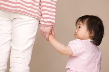 母親と手を繋いで歩いている赤ちゃん