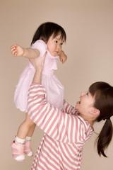 母親に持ち上げられて喜んでいる赤ちゃん