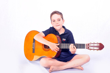 A studio shot of a young boy with an acoustic guitar