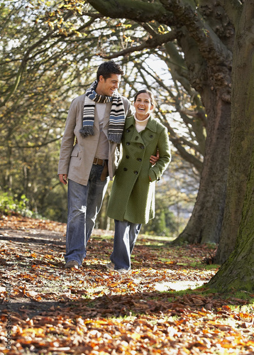 Couple outdoors arm in arm laughing in a park