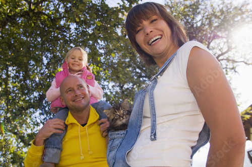 Father carrying girl on shoulder, mother holding kitten, low angle view