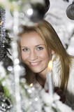 Austria, Salzburger Land, Young woman at Christmas tree, smiling, portrait, close-up