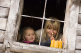 Austria, Salzburger Land, Mother and daughter (3-4) lighting candles on windowsill