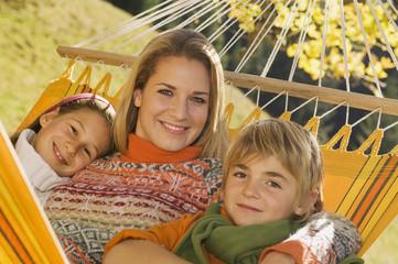 Österreich, Salzburger Land, Altenmarkt, Mutter und Kinder in der Hängematte, im Herbst