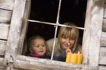 Österreich, Salzburger Land, Mutter und Tochter beim Anzünden von Kerzen