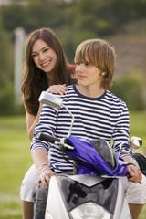 Junges Paar sitzt auf Moped, lächelnd
