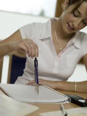 Teenager, Mädchen sitzt am Schreibtisch und zeichnet mit Zirkel
