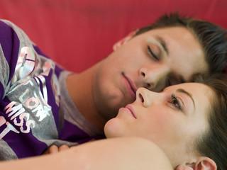 Junges Paar liegt auf dem Bett