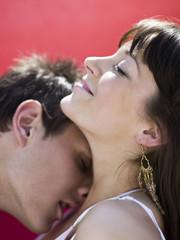 Junger Mann küsst Hals einer jungen Frau
