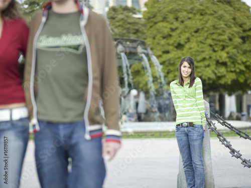 Young woman leaning on pole, watching couple