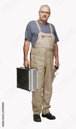 Craftsman in overall, with toolbox, portrait