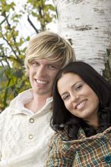 Junges Paar lehnt an Baumstamm, lächelnd