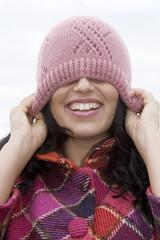 Junge Frau, Augen durch eine Kappe abgedeckt