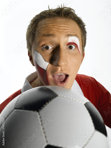 Young man with Poland flag painted on face holding soccer ball, mouth open