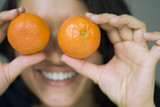 Young woman holding tangerines to eyes