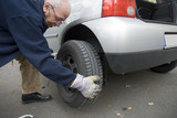 Senior man changing car tyre, close-up
