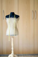 Mannequin und Maßband vor Kleiderschrank