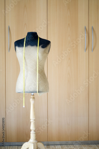 Mannequin and tape measure in front of wardrobe