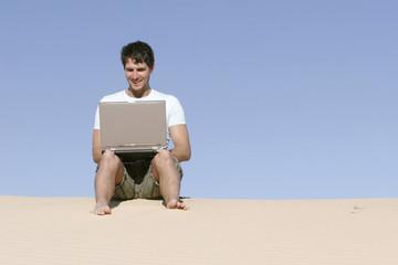 Mann sitzen auf einer Düne mit Laptop