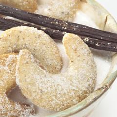 Vanillekipferl auf Tasse mit Zucker und Vanillesticks