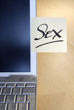 "Adhesive note on laptop saying ""Sex"""
