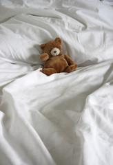 Teddybär auf Bettdecke