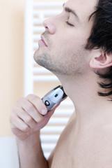 Junger Mann mit elektrischen Rasierer, Portrait