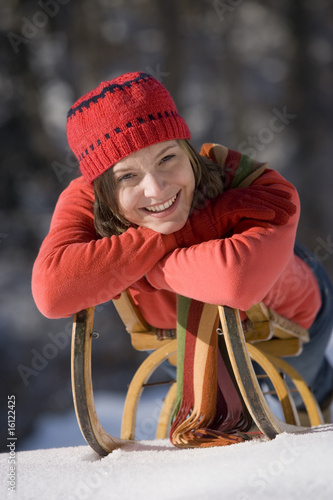 Young woman lying on sledge, portrait, smiling