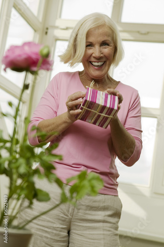 Senior woman holding gift box, smiling, low angle view