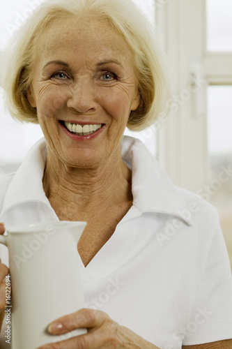 Senior woman holding jug, smiling, close-up, portrait